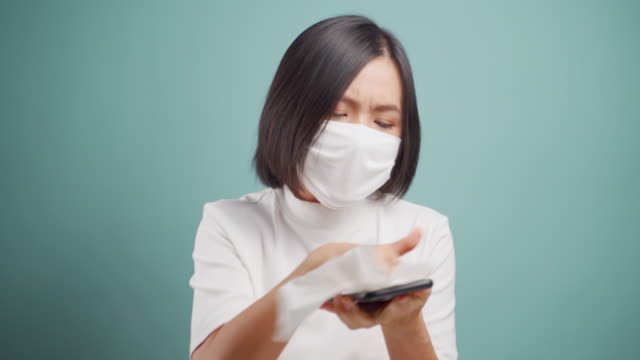 asian woman in face mask cleaning the phone using tissue paper to wipe to avoid  virus bacteria. covid-19, coronavirus concepts. - tissue paper stock videos & royalty-free footage