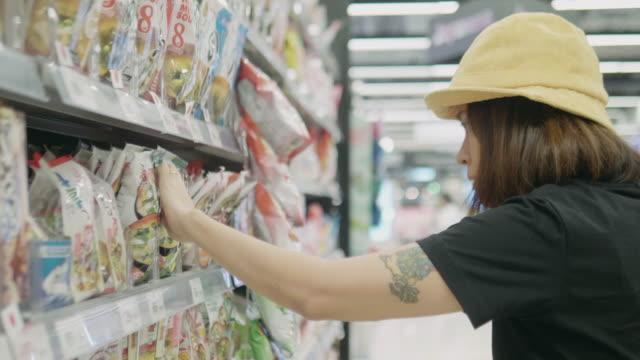 vídeos de stock, filmes e b-roll de mulher asiática em mercearia - etiqueta mensagem