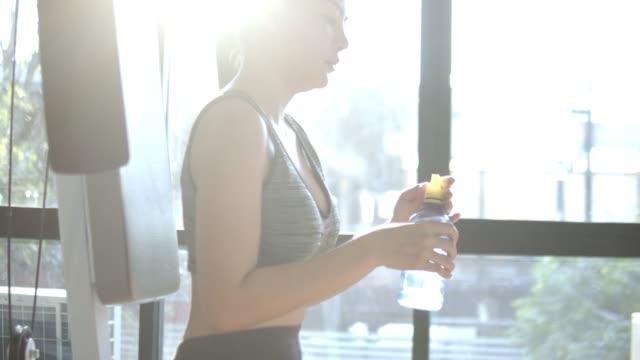 vídeos de stock, filmes e b-roll de mulher asiática no ginásio beber bebida energética - sutiã para esportes