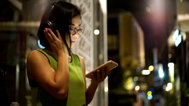 Asian woman in headphones listening to music on mobile phone while standing on street at night.