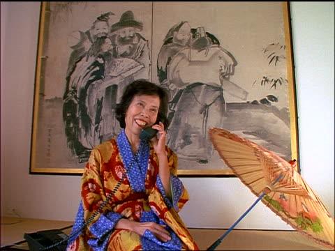 vídeos de stock, filmes e b-roll de asian woman in kimono sitting on mat + talking on telephone - só uma mulher madura