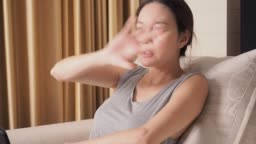 asian woman in living room using tablet got mosquito bite. female itchy and annoying, she try to hit mosquito.
