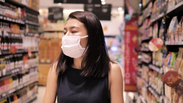 asian woman in protective mask choosing product goods, female shopping cart at supermarket covid19 pandemic - tre quarti video stock e b–roll