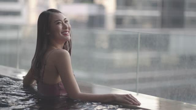 vídeos de stock, filmes e b-roll de mulher asiática de maiô está nadando em uma piscina com a cidade ao fundo durante uma longa férias de verão. - infinito