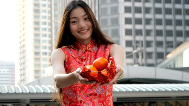 asian woman in traditional chinese red dress holding fresh oranges in red silk fabric basket. happy chinese new year concept. - religious celebration stock videos & royalty-free footage