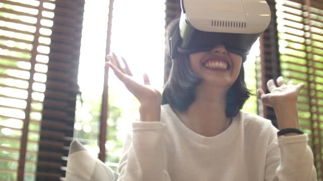 asiatische frau in virtual-reality-kopfhörer zu hause - interaktivität stock-videos und b-roll-filmmaterial