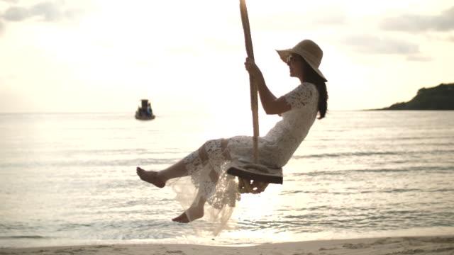 vídeos y material grabado en eventos de stock de mujer asiática con vestido blanco balanceándose en la playa - columpio