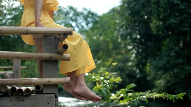 Asian woman in yellow suit relaxing, smile and sitting on a wooden pier and dangle feet over the water
