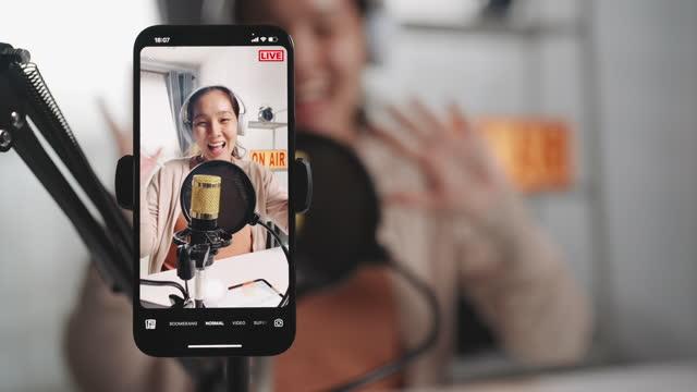asiatische influencerin mit mikrofon tragen kopfhörer aufnahme inhalte mit smartphone für online social media - content stock-videos und b-roll-filmmaterial