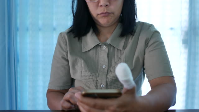 asian woman injured finger with bandage using smart phone - bandage stock videos & royalty-free footage