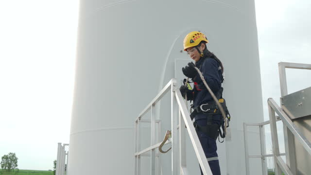 asian woman inspection engineer wearing safety harness and safety line working preparing and progress check of a wind turbine with safety in wind farm in thailand. - repairing stock videos & royalty-free footage