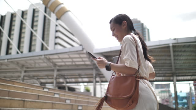 asian woman is chatting online with friends using smart phone and walking in the office building - steps and staircases stock videos & royalty-free footage