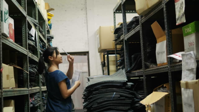 Asian woman is checking and counting box container in the storage