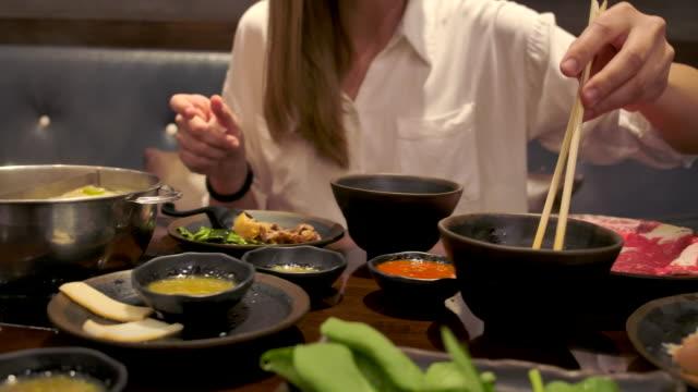 vídeos y material grabado en eventos de stock de una mujer asiática está comiendo un shabu de ternera wagyu. - comida coreana