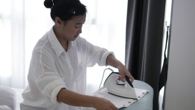 アジアの女性が寝室ストック ビデオで服をアイロンします。 - アイロン点の映像素材/bロール