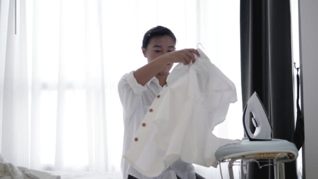 Asian woman is ironing clothes in the bedroom- Stock video
