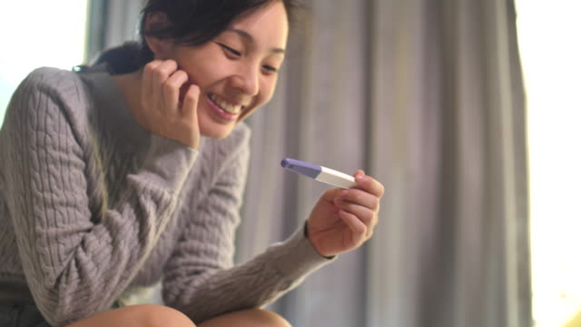 asian woman is pregnant using pregnancy test, happy feeling - pregnancy test stock videos & royalty-free footage
