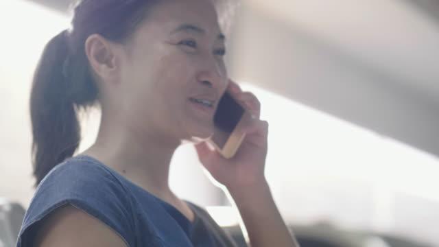 Femme asiatique parle en utilisant le téléphone intelligent sur le parking