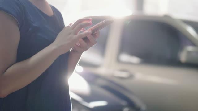アジアの女性が駐車場でスマート フォンを使用して話しています。 - 駐車場点の映像素材/bロール