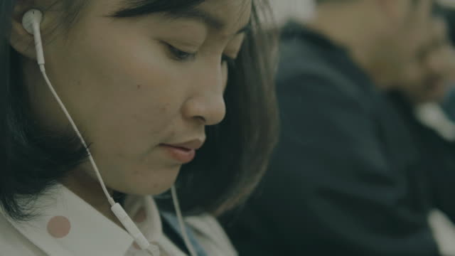 asian woman is using earphone with her mobile phone beside her friends - mp3 player stock videos & royalty-free footage