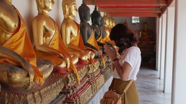 asian woman is worshiping buddha statue in pho temple in bangkok, thailand. - buddha video stock e b–roll