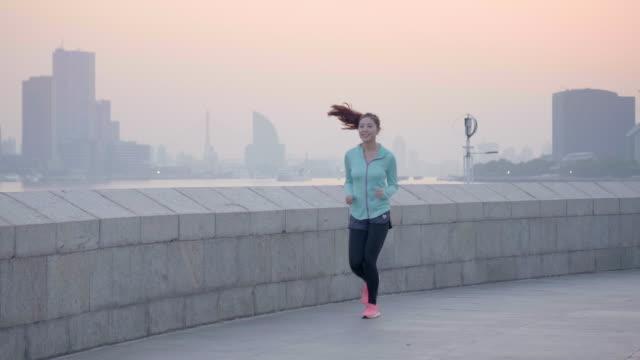 慢跑在城市設置的亞洲女人 - 商業金融與工業 個影片檔及 b 捲影像