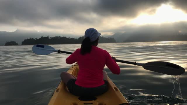 donna asiatica in kayak nel grande lago tropicale al mattino con luce del sole.sport rilassante - dorso umano video stock e b–roll