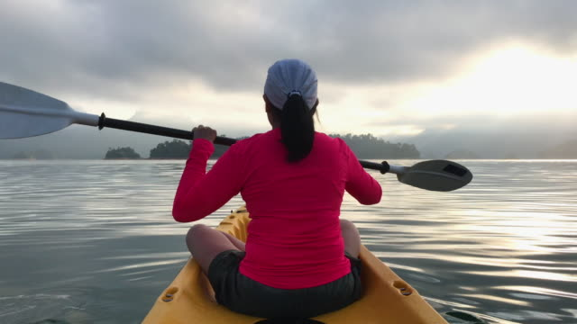 asian woman kayaking in tropical large lake in morning with sunlight.relaxing sport - dorso umano video stock e b–roll