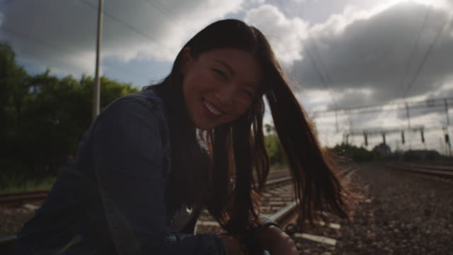 Asian woman laughing on the railroad truck.