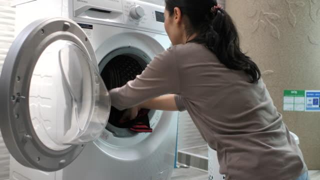 vídeos de stock, filmes e b-roll de lavanderia asiática da mulher em em casa - lavanderia edifício público