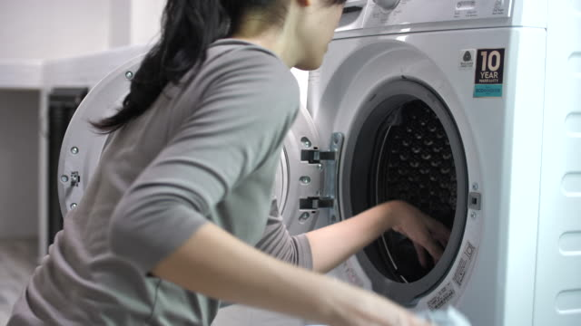アジアの女性は自宅で洗濯 - 洗濯点の映像素材/bロール