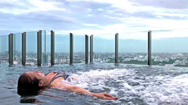 vídeos de stock, filmes e b-roll de mulher asiática que estabelece sobre o spa fonte na piscina no condomínio alto luxo - apartamento