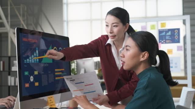 現代のオフィスでデスクトップコンピュータ上のデザイナーとモバイルアプリデザインワイヤーフレームプロトタイプのタイムラインカレンダーの締め切りについて議論するアジアの女性リ� - プロトタイプ点の映像素材/bロール