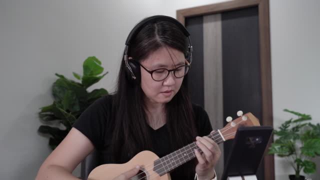 vídeos de stock, filmes e b-roll de mulher asiática aprendendo a jogar ukulele da internet auto-estudando em casa. - ukulele