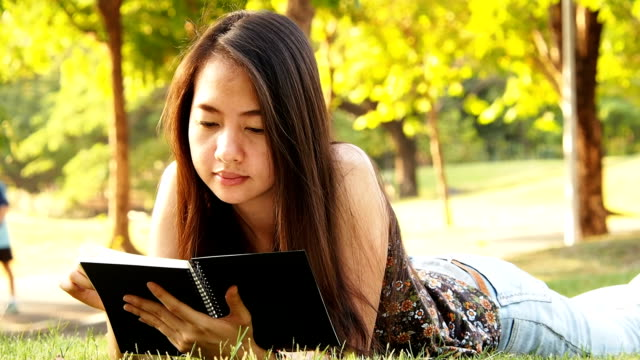 Asian woman lies on green grass and reads book