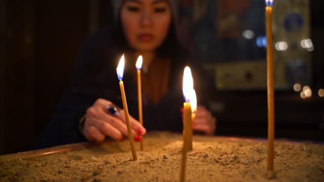 教会でろうそくを照らすアジアの女性 - 懺悔点の映像素材/bロール