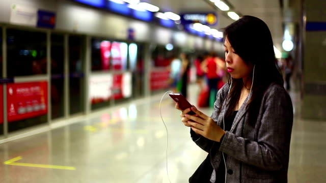 Asian woman listening music at subway station.
