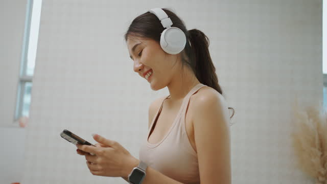 asian woman listening music by headphone when exercise at home. - bluetooth stock videos & royalty-free footage