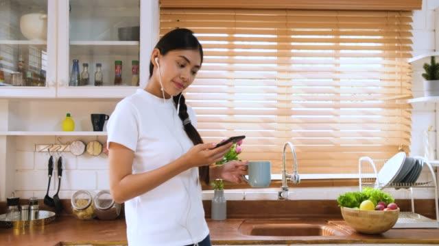 アジアの女性の携帯電話とキッチンでコーヒーを飲むカップ音楽を聴いてリラックスします。 - 台所点の映像素材/bロール