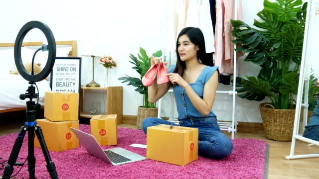 4K. Asian woman live streaming for selling shoe, fashion accessories online on social media via mobile phone from bedroom at home. owner of small business working from home during self isolation