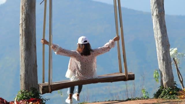 Regard de femme asiatique à mountain view en Thaïlande sur la balançoire, slow motion, solo de femme Concept voyage