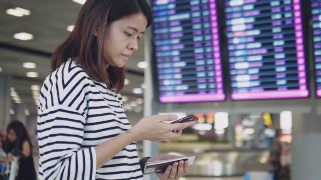 アジアの女性は空港出発ボードを見て - 飛行機の搭乗券点の映像素材/bロール