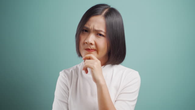 asian woman looking at camera thoughtful negative tinking and standing isolated over blue background. 4k video. emotional conceps. - decisions stock videos & royalty-free footage