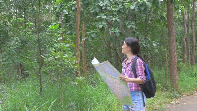 Aziatische vrouw kaart kijken en wandelen in het bos