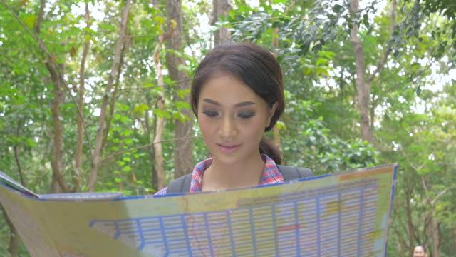 Aziatische vrouw kijken naar kaart in bos