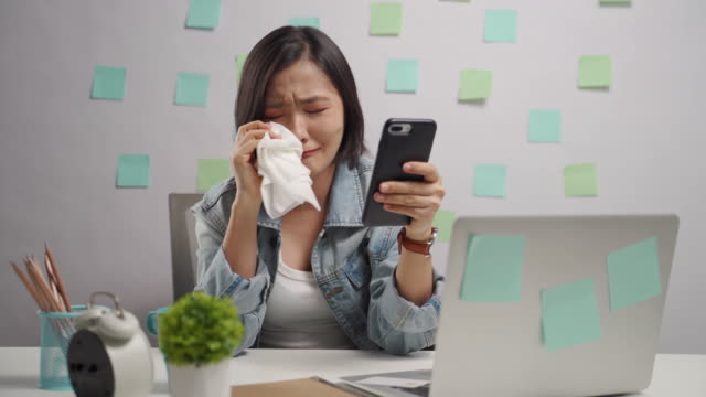 asian woman looking at smart phone reading news crying and using tissue paper at home office. wfh. work from home. - tissue paper stock videos & royalty-free footage