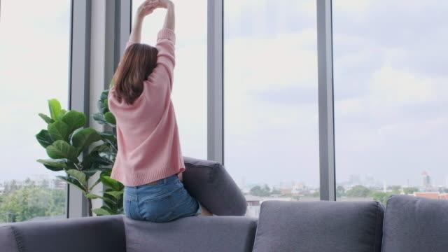 vidéos et rushes de femme asiatique à la recherche en vue de la fenêtre et qui s'étend et sortent du cadre à condiminum.panning tiré - admirer le paysage
