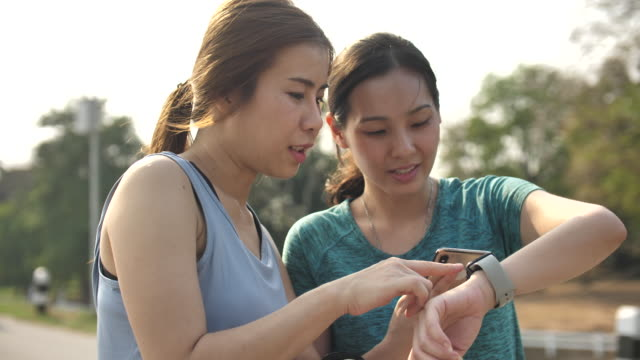 asian woman looking data on smart watch exercising with friend - smart watch stock videos & royalty-free footage