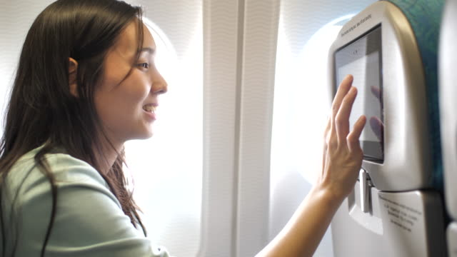 asian woman looking entertainment at display on airplane, in-flight entertainment - arts culture and entertainment stock videos & royalty-free footage