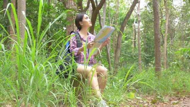 Aziatische vrouw op kaart Zoek in bos. Aziatische vrouwen reizen buiten levensstijl in bos